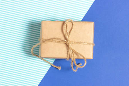Gift box wrapped in kraft paper on a blue background. Top view, holiday concept.