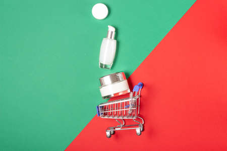 A set of face and body cosmetics and a shopping trolley on a bright red and green background. The concept of buying cosmetics, online store, holiday