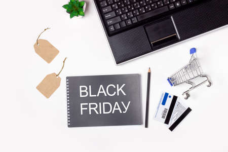 Black Friday. Laptop, note book and shopping trolley on a white background. Online shopping concept
