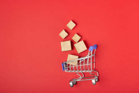 Shopping basket and boxes with purchases with place to add text on a red background. Online shopping and sale concept
