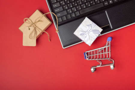 Laptop, notebook, shopping cart and boxes on a bright red background. Online shopping concept Zdjęcie Seryjne