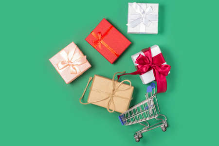 Gift boxes lie in a shopping basket. Gift shopping concept, online store