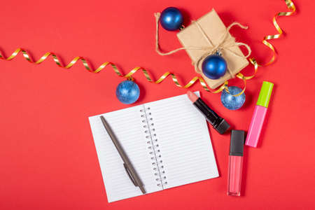 Open blank notebook with place to add text, shopping cart and boxes on a bright red background. Online shopping concept
