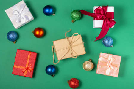 Bright gift boxes and Christmas decorations, on a green background. Top view, holiday and Christmas concept.