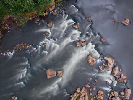 From above view of river rapids, long exposure. Water flow. Aerial top view of stream.