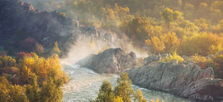 Autumn sunny rock canyon and river with rapids in golden sunrise light.