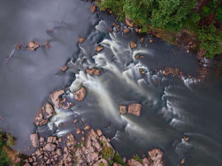 From above view of river rapids, long exposure. Aerial top view of stream. Water flow. Фото со стока