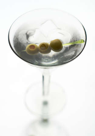 Martini with olive on fancy skewer, isolated on white.  Stock Photo - 5771335