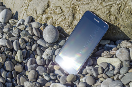 Smartphone On The Pebbly Sea Beach In Summer