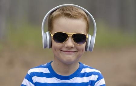 Smiling Little Boy In Headphones Outdoor
