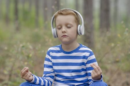 boy sitting: Little Boy Meditating In The Forest Stock Photo