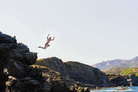 Fitness body young age man jumping into the void (bottom is not seen) from a rock, concept of freedom and