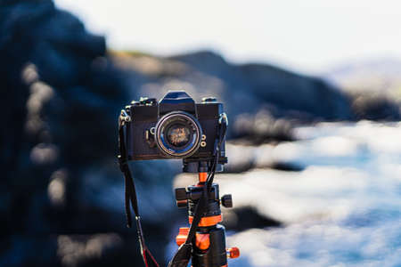 Black unbranded reflex (analog) camera planted on a tripod facing the camera. With a seascape in the background on a sunny summer day.