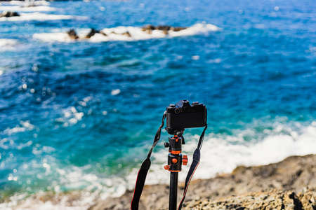 Black (analog) unbranded reflex camera planted on a tripod, taking pictures of the seascape on a sunny day.