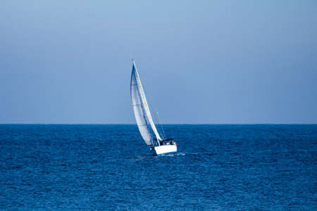 A white sailboat in the middle of the calm sea and under a wide clear blue sky.