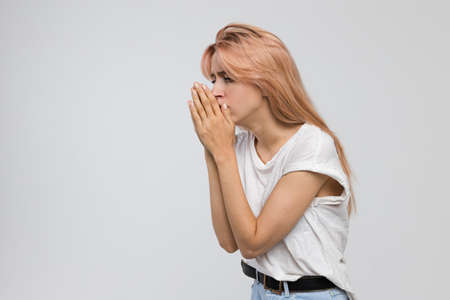 Studio portrait of a young girlfriend coughing student feeling cold, bronchitis, sore throat, feeling of the first. Stock Photo
