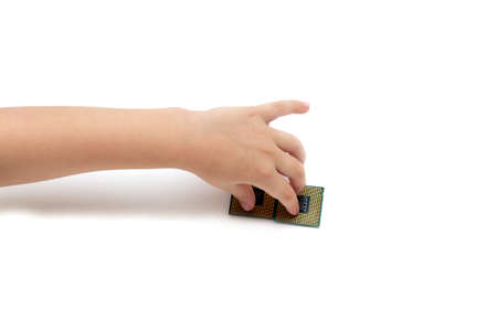 Childs hand holds intel computer central processing units isolated on white background pins up socket 775, young professional concept, technology for children how to play toys.