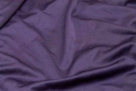 texture background uneven with folds T-shirt cotton and polyester fabric in dark blue