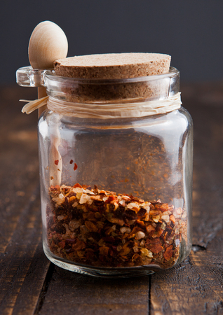 lemony: Jar with spices and small spoon on wooden board. Various spices