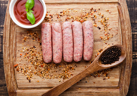 charcutería: Raw beef sausages with pepper spoon and sause on board. Spices for beef. Basil in sause Foto de archivo