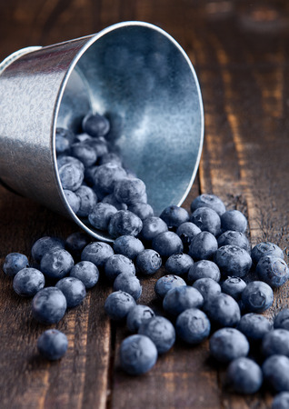 steel bucket: Blueberries in small steel bucket on grunge wooden board. Natural healthy food