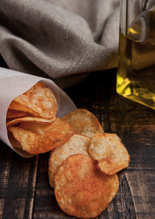 potato crisps: Bowl with potato crisps chips and olive oil on wooden board. Junk food