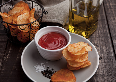 paprica: Potato crisps with ketchup on plate and olive oil. Wooden background Stock Photo