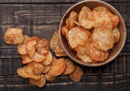 potato crisps: Bowl with potato crisps chips on wooden board. Junk food