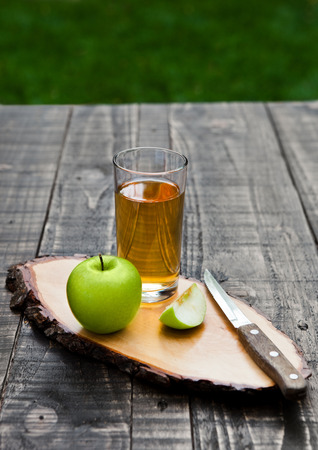 Apple juice glass with healthy green apples on kitchen board. Outside in garden Stock Photo