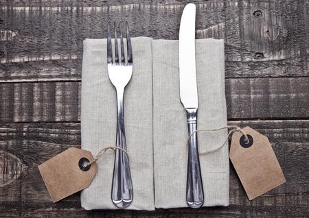 Messer und Gabel in Küchentuch auf Holzbrett. Platz für Text