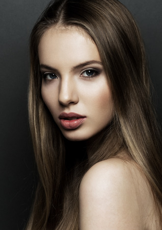 Beautiful woman model portrait with long hair on black background. Red lips