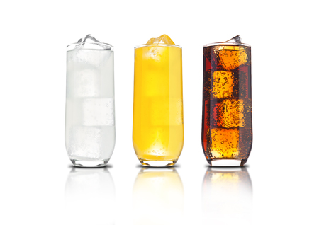 Glasses of orange soda, cola and lemonade with ice cubes and bubbles with reflection on white background