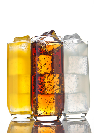 Glasses with cola orange soda and lemonade with ice cubes and reflection on white background