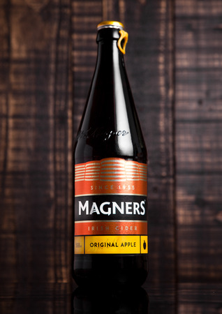 county tipperary: London, England - September 11, 2016: Bottle of Magners Original Irish Cider, produced in County Tipperary in Ireland by the C&C Group. With wooden background