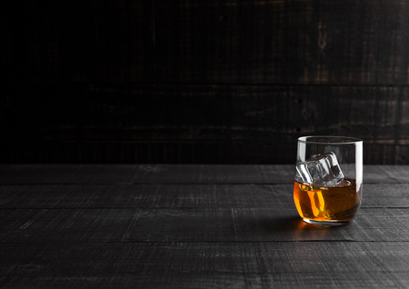 Glass of whiskey with ice cubes on wooden background