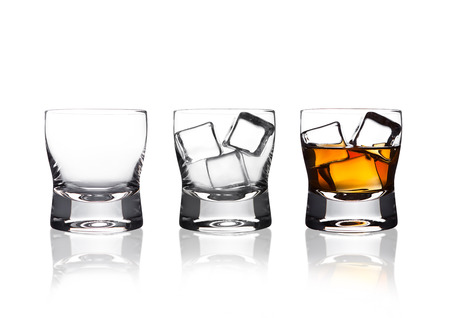 Glasss of whiskey with ice cubes with reflection on white background Stock Photo