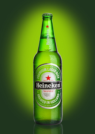 LONDON,UK -OCTOBER 23, 2016: Bottle of Heineken Lager Beer on green background. Heineken is the flagship product of Heineken International
