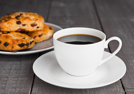 Cup of coffee with fresh fruit scones with raisins on wooden table Imagens