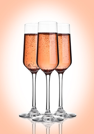 Glass of pink rose champagne with bubbles on pink background