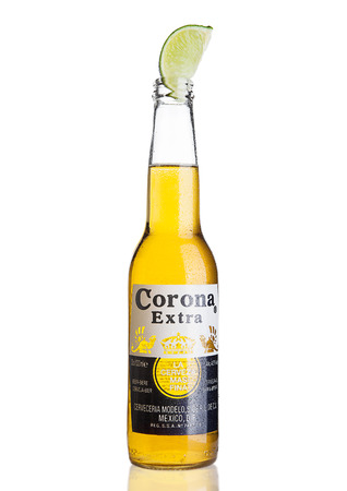 LONDON, UNITED KINGDOM - NOVEMBER 04, 2016: Bottle of Corona Extra Beer with lime slice.Corona, produced by Grupo Modelo with Anheuser Busch InBev, is the most popular imported beer in the US.