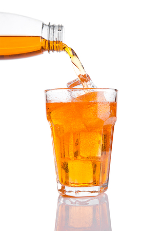 Pouring orange energy soda drink in glass with ice on white background Stock Photo