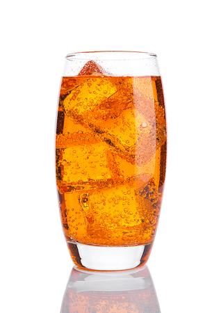 Glass of orange energy soda drink with ice on white background