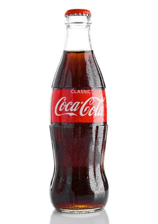 LONDON, GROSSBRITANNIEN - 7. NOVEMBER 2016: Klassische Flasche Coca-Cola auf weißem Hintergrund mit Weihnachtsspielwaren und -schnee