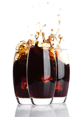 Glasses of cola with splash and ice cubes on white background