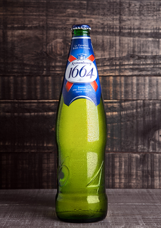 illustrative: LONDON, UK- NOVEMBER 15 ,2016. Cold bottle of Kronenbourg 1664 beer on wooden background. A 5.5% pale lager is the main brand of Kronenbourg Brewery owned by the Carlsberg Group
