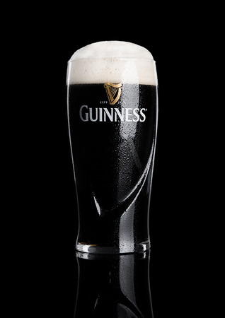 guinness beer: LONDON, UK - NOVEMBER 29, 2016: Glass of Guinness original beer on black background. Guinness beer has been produced since 1759 in Dublin, Ireland.