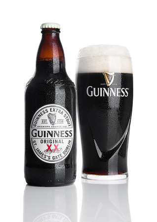 cerveza negra: LONDON, UK - NOVEMBER 29, 2016: Guinness extra stout beer bottle and glass on white background. Guinness beer has been produced since 1759 in Dublin, Ireland.