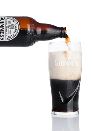 guinness beer: LONDON, UK - NOVEMBER 29, 2016: Guinness extra stout beer bottle on white background. Guinness beer has been produced since 1759 in Dublin, Ireland. Editorial