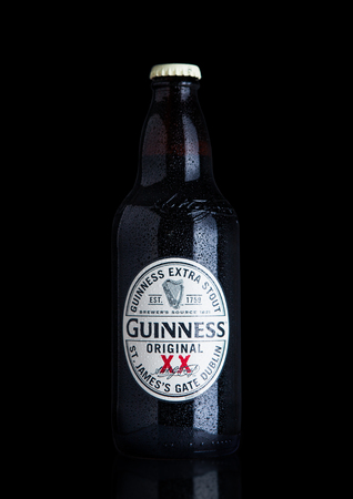 cerveza negra: LONDON, UK - NOVEMBER 29, 2016: Guinness extra stout beer  bottle on black background. Guinness beer has been produced since 1759 in Dublin, Ireland. Editorial