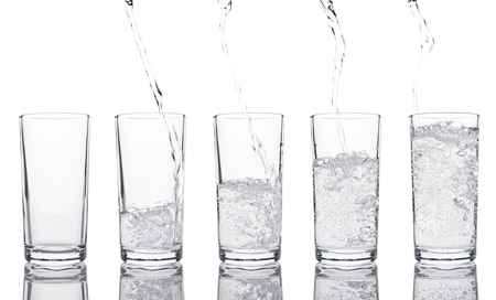 Pouring fresh healthy sparkling water to glass on white background